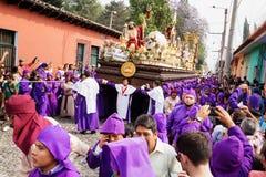 Lilor rånade män som bär en flöte med Kristus och ett kors på processionen av San Bartolome de Becerra, Antigua Royaltyfri Foto