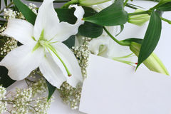Lily bouquet and greeting card. White lily bouquet and blank greeting card close-up Stock Image