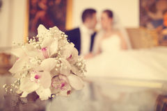 Lily bouquet on table with bride and groom as silhouettes Royalty Free Stock Photography