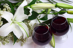 Lily bouquet and two glasses of red wine. White lily bouquet two glasses of red wine close-up Royalty Free Stock Image