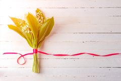 Lily flower bouquet tied with red ribbon on white wooden background. With copy space Stock Images