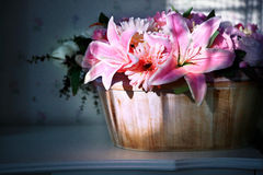 Lily flower in wood bucket with cookie light Royalty Free Stock Photography
