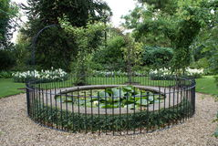 Lily pond with rose arches and railing Royalty Free Stock Image
