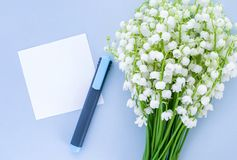 Lily of the valley on a blue background, an empty sheet of paper and a marker. Top view, empty space for text royalty free stock images