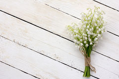 Lily of the valley bouquet of white flowers tied with string on a white background barn boards Royalty Free Stock Photo