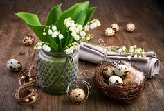 Lily of the valley and Easter decorations on old oak wood Stock Photos