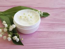 Lily of the valley flower products cosmetic on pink wooden. Lily of the valley flower cosmetic on pink wooden treatment products Royalty Free Stock Image