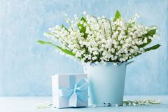 Lily of the valley flowers in blue vase and gift box on rustic table. Greeting card for woman day. Lily of the valley flowers in blue vase and gift box on table royalty free stock photography