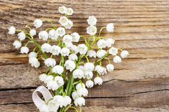Lily of the valley flowers on wooden background. Royalty Free Stock Photos