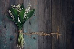 Lily of the Valley on old wooden table stock photography