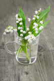Lily of the valley in transparent glass on wood Stock Photo