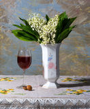 Lily of the valley in vase, glass of wine and candies Stock Photo