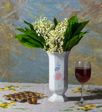 Lily of the valley in vase, glass of wine and candies Royalty Free Stock Images