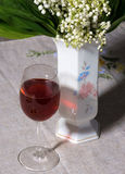 Lily of the valley in vase and glass of wine Stock Photos