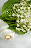 Lily-of-the-valley and wedding ring. Lily-of-the-valley bouquet with wedding ring Royalty Free Stock Photo