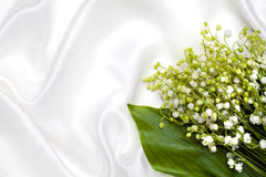Lily of the valley and white silk background Stock Images