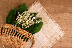 Lily of the valley, woven bag, burlap. White lily of the valley in a glass vase and background Stock Photography