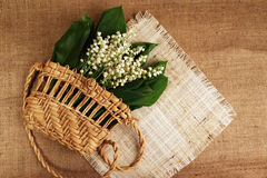 Lily of the valley, woven bag, burlap2. White lilies of the valley in a woven bag on burlap Royalty Free Stock Image