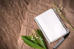 Lily of valleys, blank notepad and pens on sackcloth. Texture royalty free stock photo