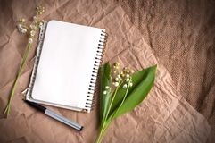 Lily of valleys, blank notepad and pens on sackcloth texture stock photography
