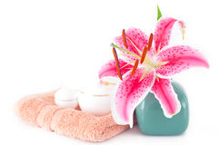 Lily in a vase, towel and cosmetic containers Stock Photos