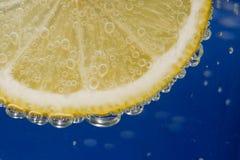 Limão amarelo na água azul Imagem de Stock Royalty Free
