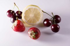 Limão, cerejas e morangos no fundo branco Fotografia de Stock