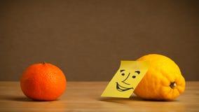 Limão com a nota de post-it que sorri na laranja Imagens de Stock