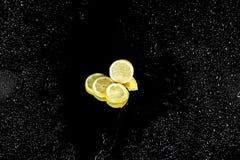 Limão cortado fresco com gotas da água isolado no preto Fotos de Stock Royalty Free