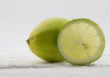 Limão e fatia inteiros no fundo de madeira branco rústico Imagens de Stock Royalty Free