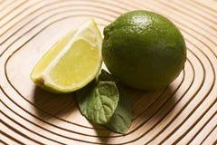 Limão e hortelã verdes no fundo de madeira Foto de Stock