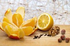 Limão e laranja na tabela de madeira com nozes, avelã e cravos-da-índia Foto de Stock Royalty Free