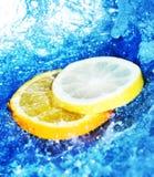 Limão e laranjas com água Fotografia de Stock