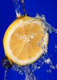 Limão e uvas-do-monte na água Fotos de Stock