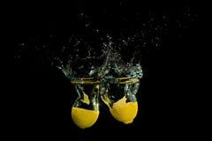 Limão na água no fundo preto Imagens de Stock Royalty Free