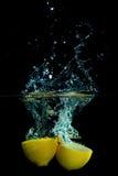 Limão na água no fundo preto Fotografia de Stock