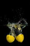 Limão na água no fundo preto Imagens de Stock