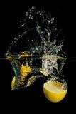 Limão na água no fundo preto Foto de Stock Royalty Free