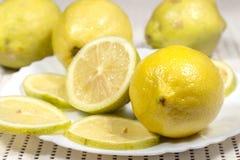 Limão no prato branco ao lado da meias parte e fatias Imagens de Stock