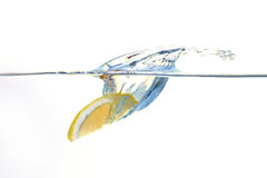 Limão que cai na água com um respingo Fotos de Stock Royalty Free