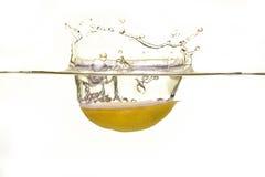 Limão que cai na água com um respingo Imagens de Stock Royalty Free