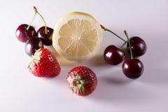 Limón, cerezas y fresas en el fondo blanco Fotografía de archivo