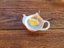 Limón cortado en la placa de la tetera en el fondo de madera Fotos de archivo