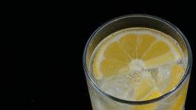Limón cortado en un vidrio largo con los cubos de hielo y soda fría en un cierre negro del fondo encima de la visión Limonada de  metrajes
