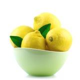 Limón en cuenco verde en blanco imagen de archivo