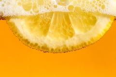 Limón en las burbujas de la cerveza Imágenes de archivo libres de regalías