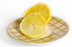Limón en un platillo del té Foto de archivo