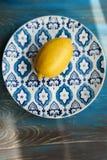 Limón fresco amarillo en la placa con el modelo azul Imagenes de archivo