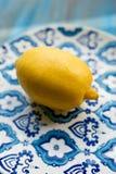 Limón fresco amarillo en la placa con el modelo azul Foto de archivo libre de regalías