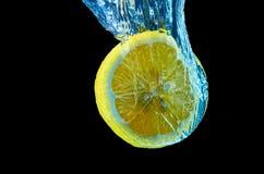 Limón fresco que cae en agua con el chapoteo en fondo negro foto de archivo